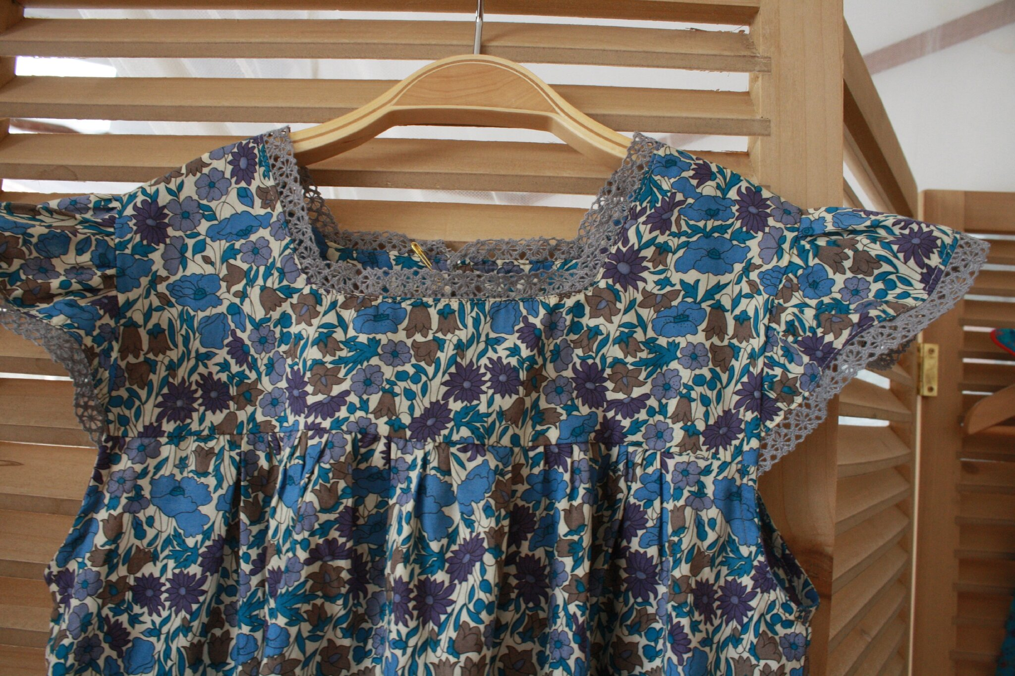 robe Liberty bleue, petites manches volantées, décolletée carrée, soulignée de dentelle grise en coton, poche devant