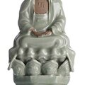 A rare moulded 'longquan' celadon figure of buddha shakyamuni, china, ming dynasty, 15th century