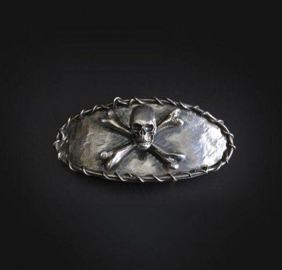 Boucle de ceinture en argent surmontée d'un crâne et de tibias croisés.