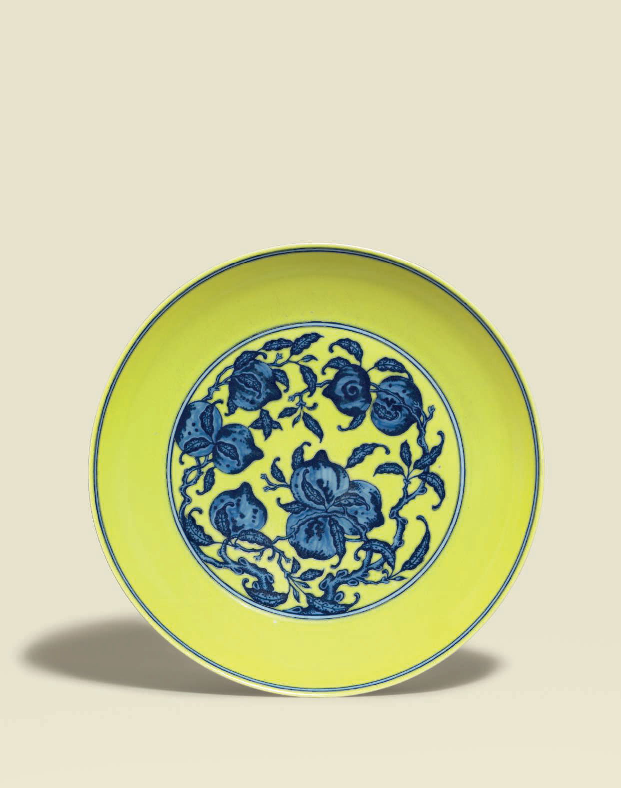 A large finely painted yellow-ground blue and white 'Nine Peaches' dish, Qianlong six-character seal mark and of the period