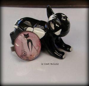 bague cabochon verre chat noir assis fond rose