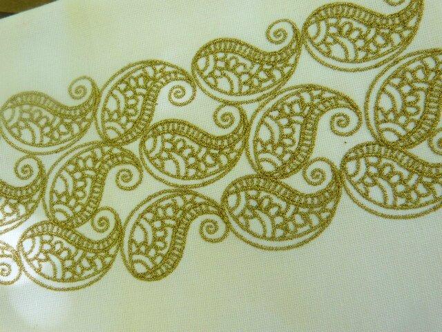 décor Nespresso(R) broderie dorée sur fond blanc