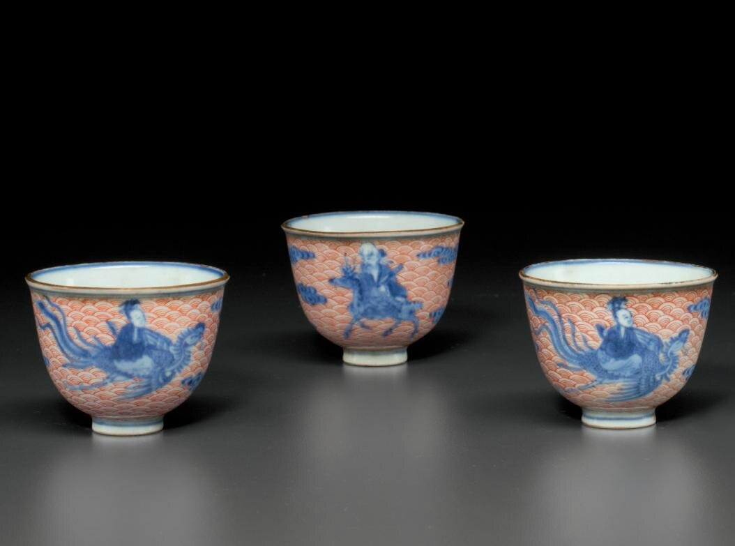 A set of three iron-red-decorated blue and white wine cups, Qianlong four-character seal marks and of the period