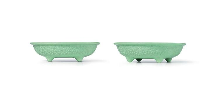 A rare pair of carved green-glazed 'Narcissus' bowls, seal marks and period of Qianlong