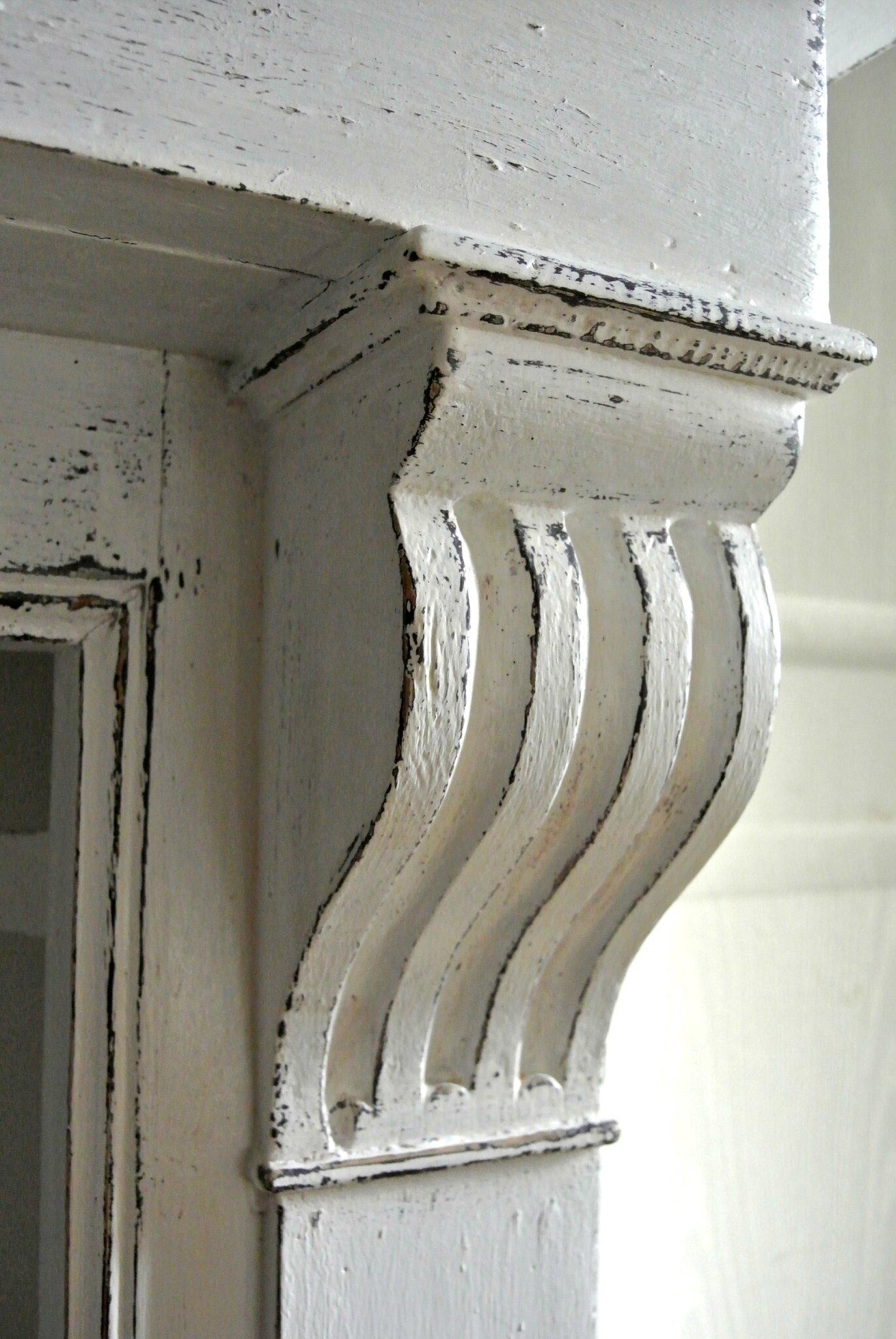 Détail manteau de cheminée patiné blanc