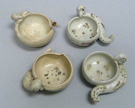 A group of four molded parrot bowls with enamel decoration. Late