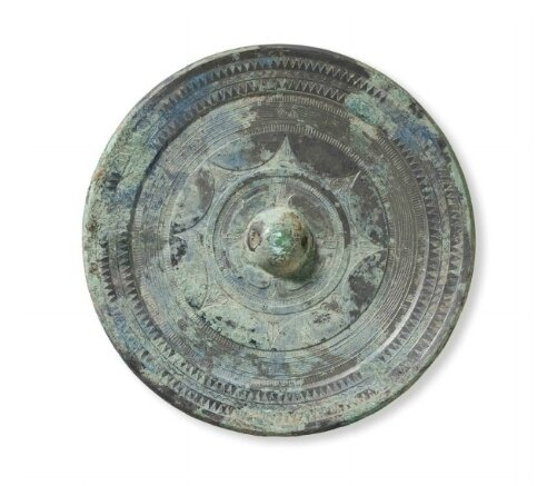 A silvery bronze circular mirror with joined arcs, China, Early Eastern Han dynasty, 1st century AD