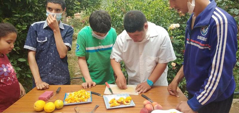 Abdelghani ramasse les derniers morceaux d'abricots qu'il a découpés
