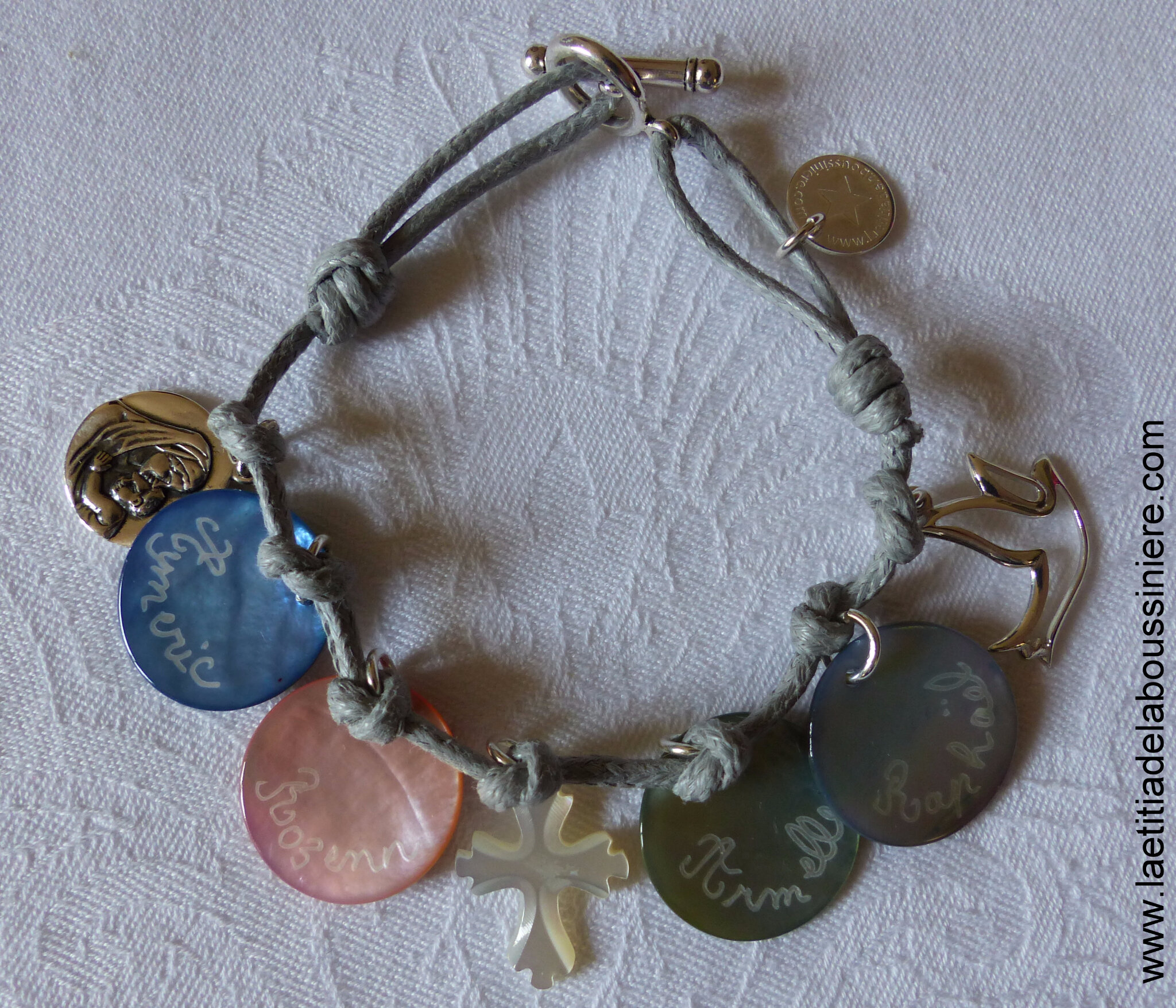 Bracelet personnalisé sur cordon composé de 4 médailles en nacre gravées, une médaille de Vierge à l'Enfant en argent, une Croix en nacre et une colombe en argent
