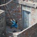 Une petite fille fait de la balancoire sur le toit d'un immeuble