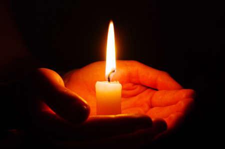13174279-la-combustion-de-la-bougie-dans-une-main-dans-l-obscurité