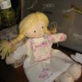 Une petite poupée en tissu et sa jolie chemise de nuit.