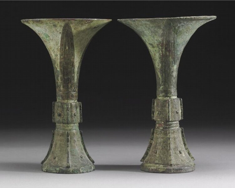 A pair of archaic bronze ritual wine vessels, gu, Shang dynasty, 13th century BC