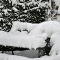 Banc du jardin habillé d'un confortable coussin neigeux