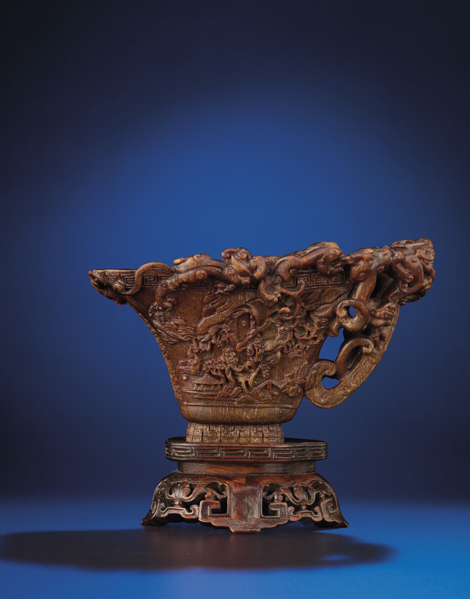 A rare and finely carved 'Nine dragons' rhinoceros horn libation cup, Ming dynasty, early 17th century