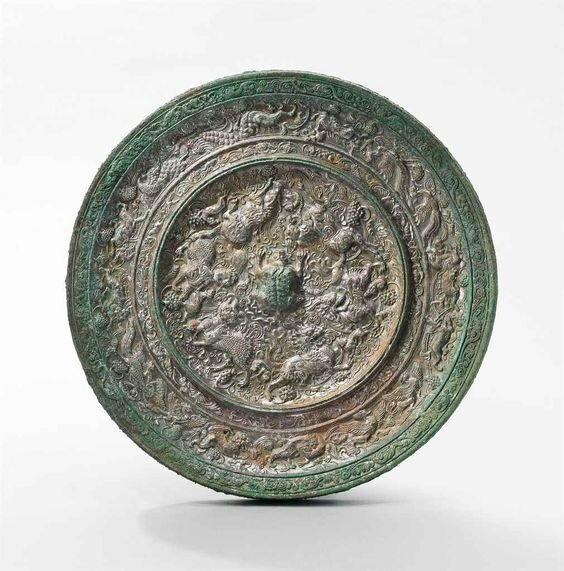 A very rare large 'Mythical Animals and Grapes' bronze mirror, Tang dynasty (618-907)