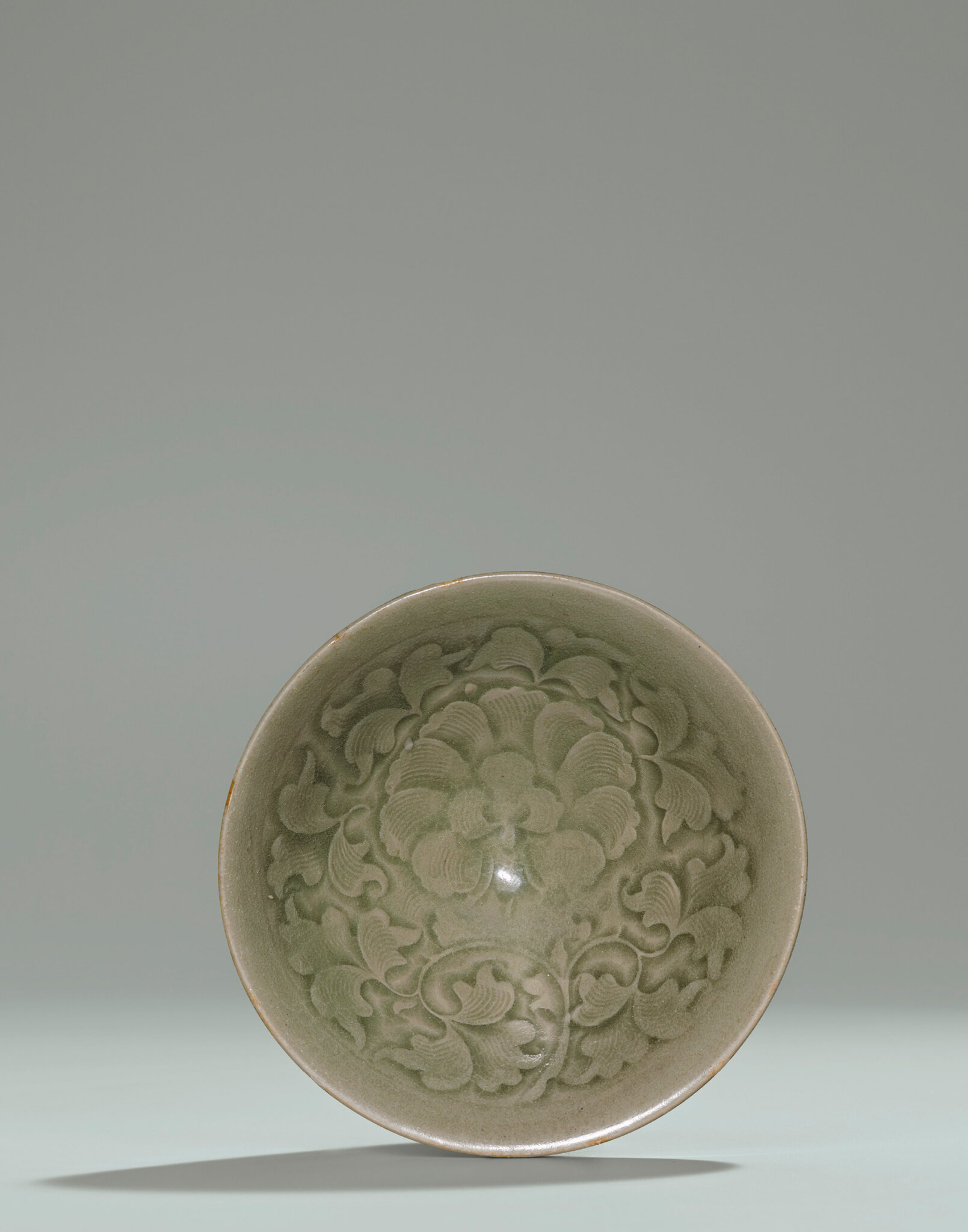 A Yaozhou carved celadon 'Peony' conical bowl, Northern Song Dynasty (960-1127)