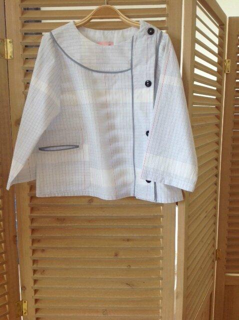 Blouse d'écolier, en tissu à carreaux de cahier, poche passepoilée, 4 ans, 35€. Personnalisable pour 5€ supplémentaire.