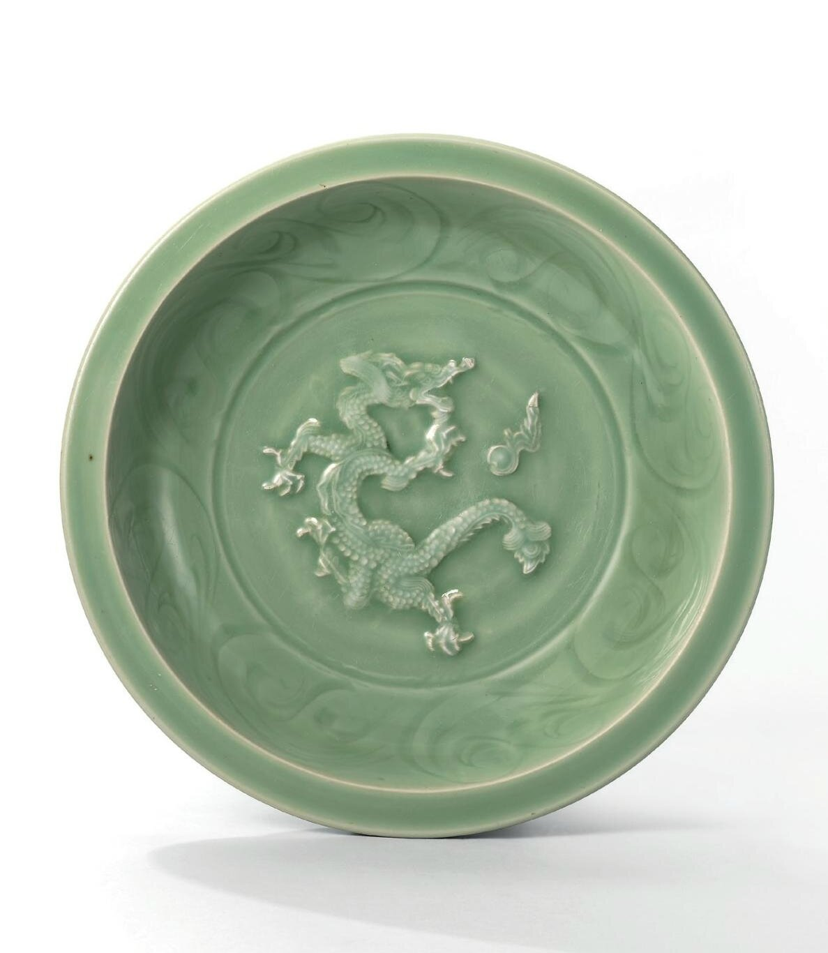 A rare carved and moulded 'dragon' charger, Yuan dynasty (1279-1368)