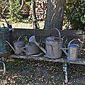 Alignement d'arrosoirs et d'anciens pulvérisateurs sur un banc