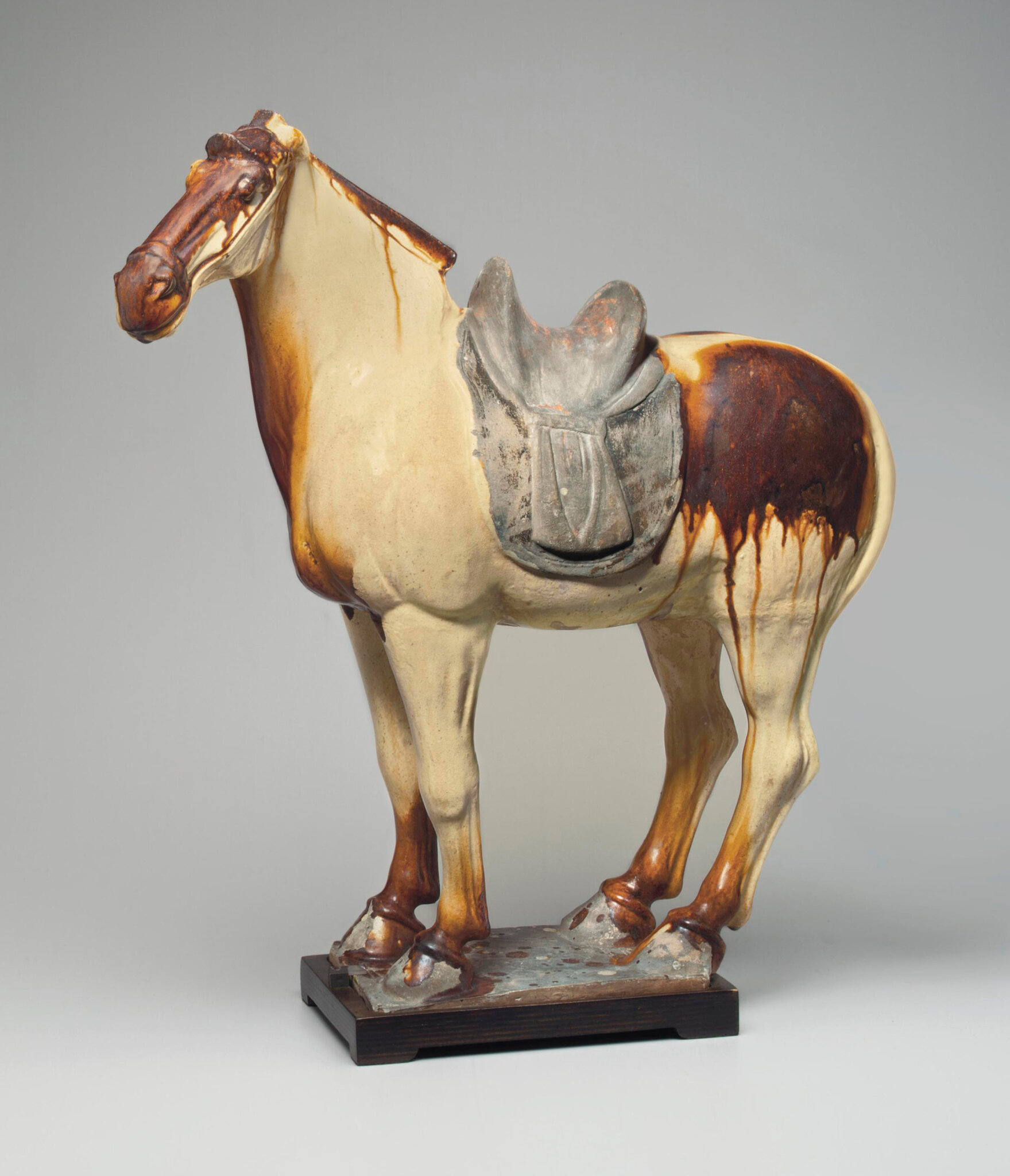 A chestnut and straw-glazed pottery figure of a horse, Tang dynasty (618-907)