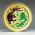 A green and aubergine-enamelled yellow-ground saucer-dish, aubergine kangxi six-character mark and of the period (1662-1722)