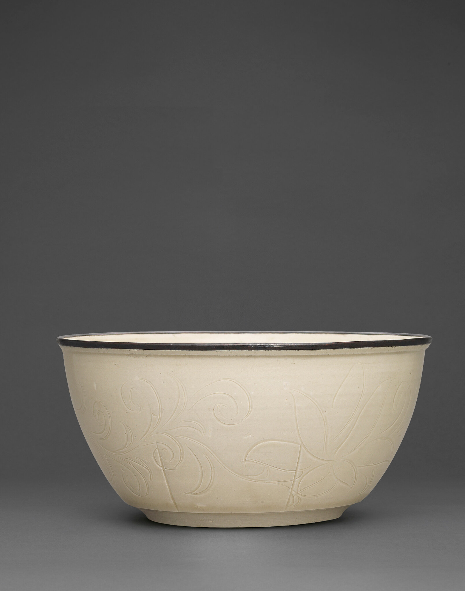 A magnificent and superbly carved large Ding 'fish' basin, Northern Song dynasty (960-1127)