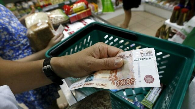 russie-crise-rouble-economie-a-customer-holds-a-russian-5-000-rouble-banknote-at-a-grocery-shop-in-krasnoyarsk_5400551