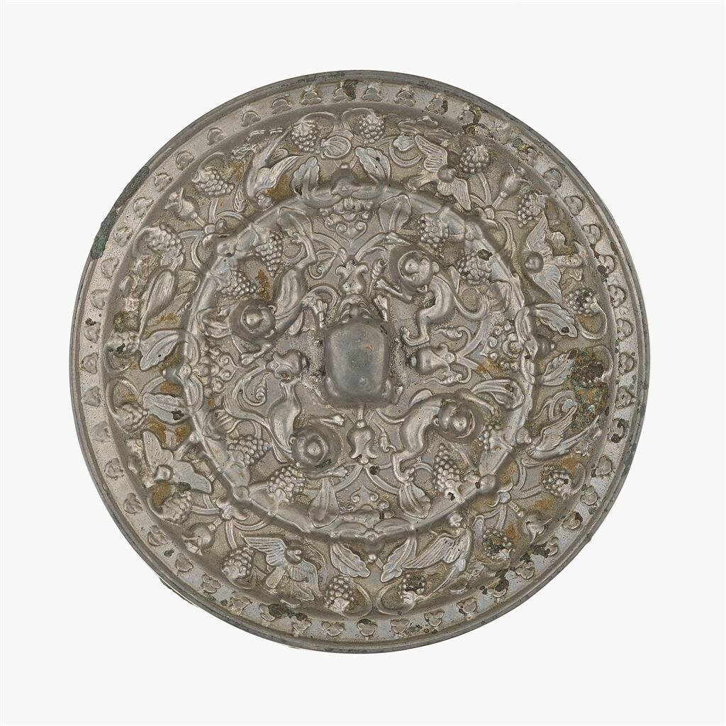 A Chinese silvery bronze circular 'lions and grapevine' mirror, Tang dynasty