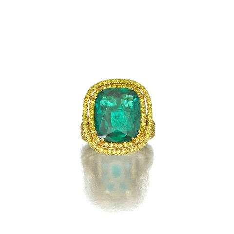 An emerald and colored diamond ring
