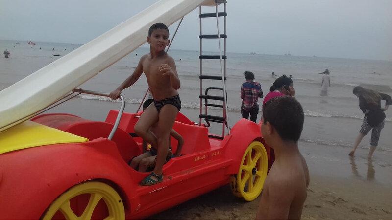 Brahim sur une voiture en forme de jeu de plage