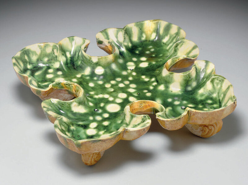A rare resist-decorated green, cream and amber-glazed pottery quatrefoil footed dish, Tang dynasty (618-907)