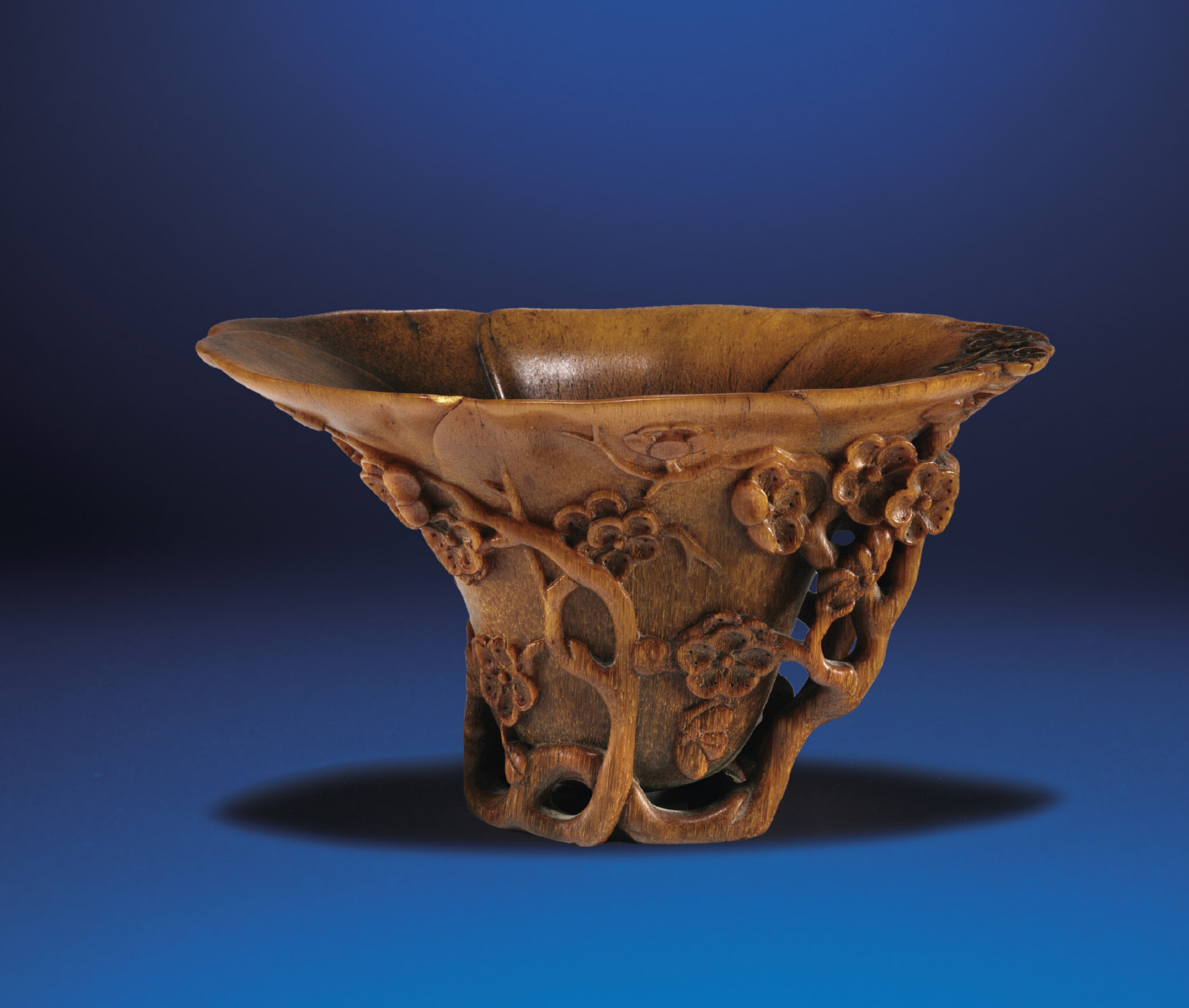 A carved rhinoceros horn 'Prunus' libation cup, Qing dynasty, 18th century