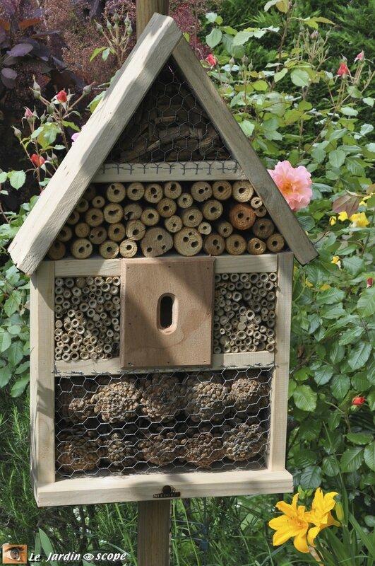 Petite maison à insectes dans un massif de fleurs
