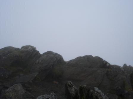 mont snowdon en plein dans la brume derrière les rochers