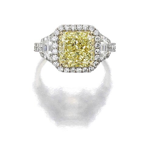 A fancy yellow diamond and diamond ring